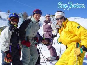 Un groupe de jeunes tout sourire devant le photographe sur une piste de ski